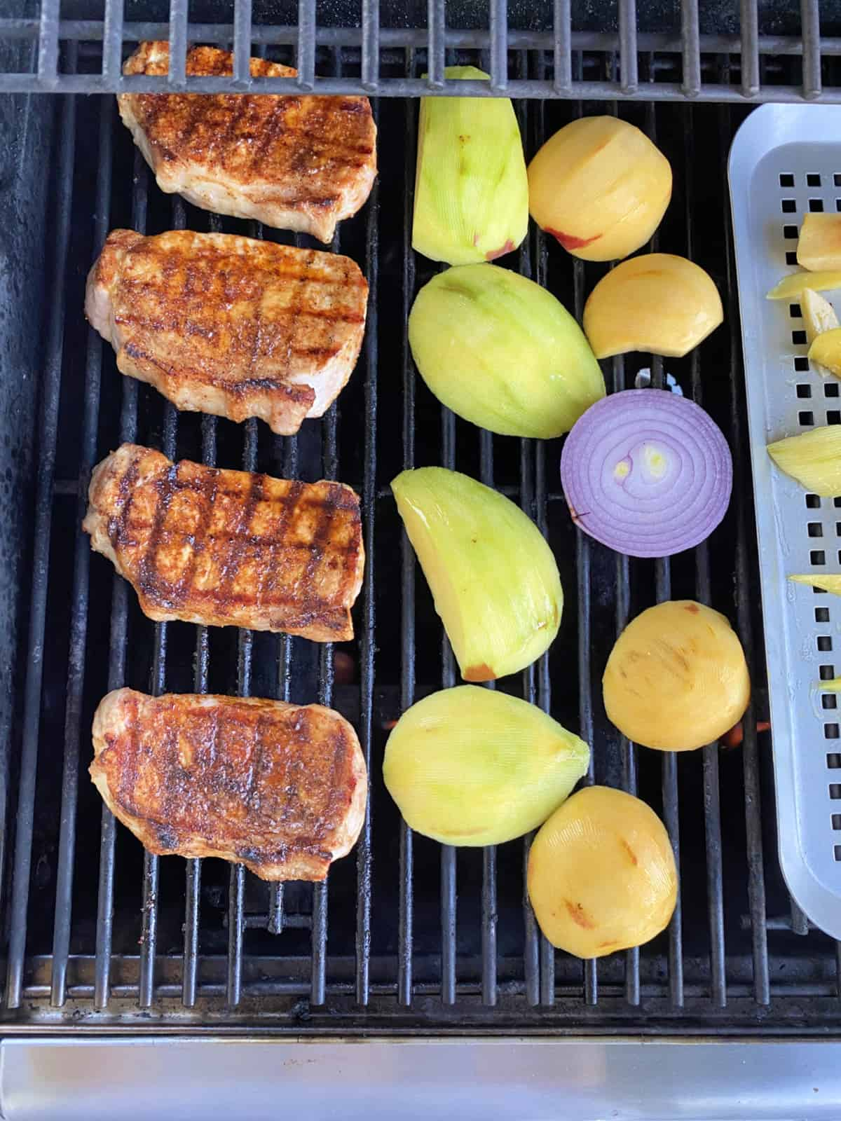 Top view of 4 grilled pork chops, sliced fruit and a red onion on a grill.