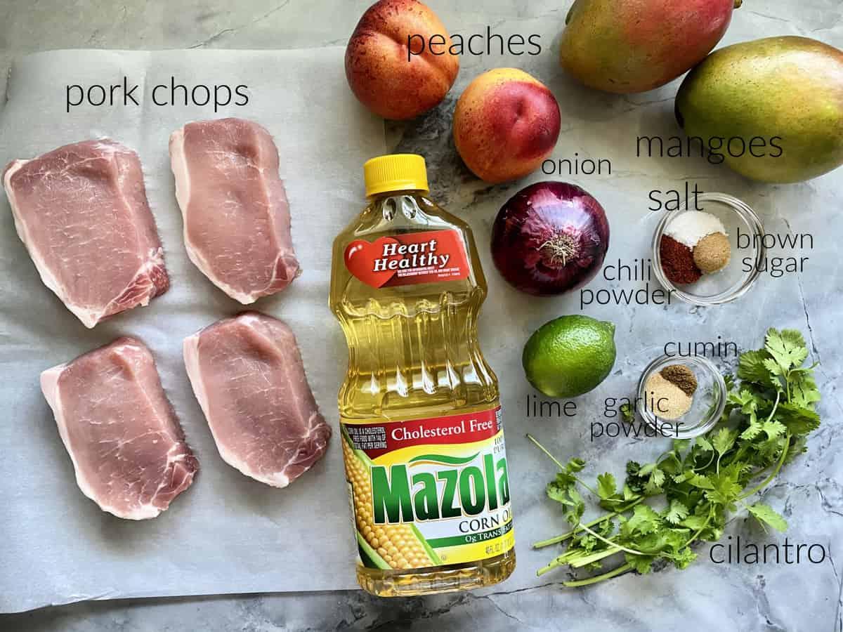 Ingredients: pork chops, Mazola® Corn Oil, peaches, onion, lime, garlic powder, cilantro, seasonings, and mangoes.