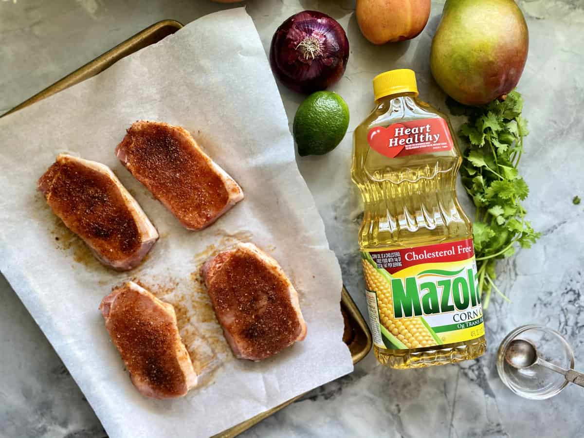 Baking sheet lined with white parchment paper with raw seasoned pork chops with fruit and a bottle of Mazola® Corn Oil next to it.
