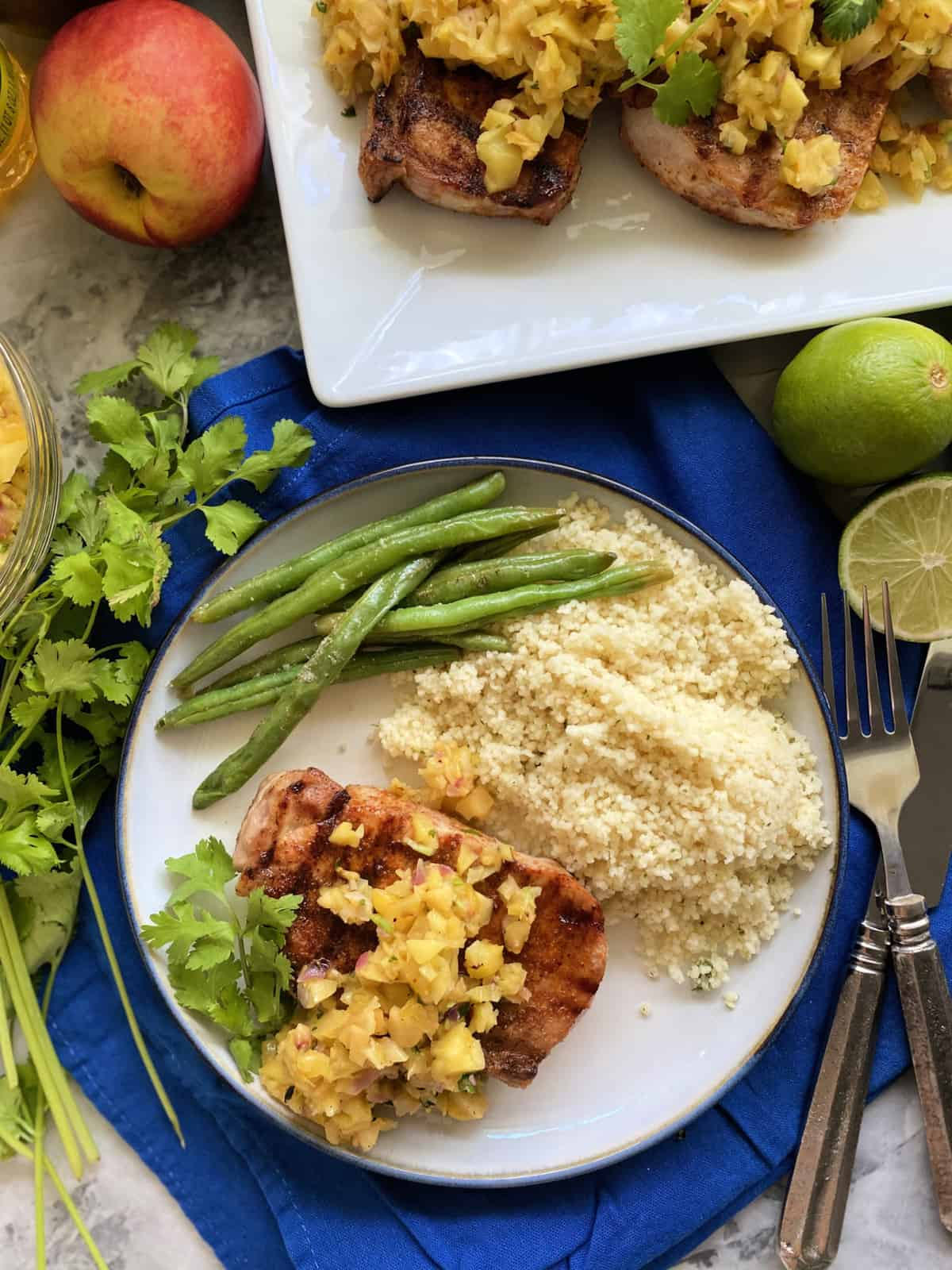 Top view of a plate and platter of pork chops, fruit salsa, couscous, and green beans.