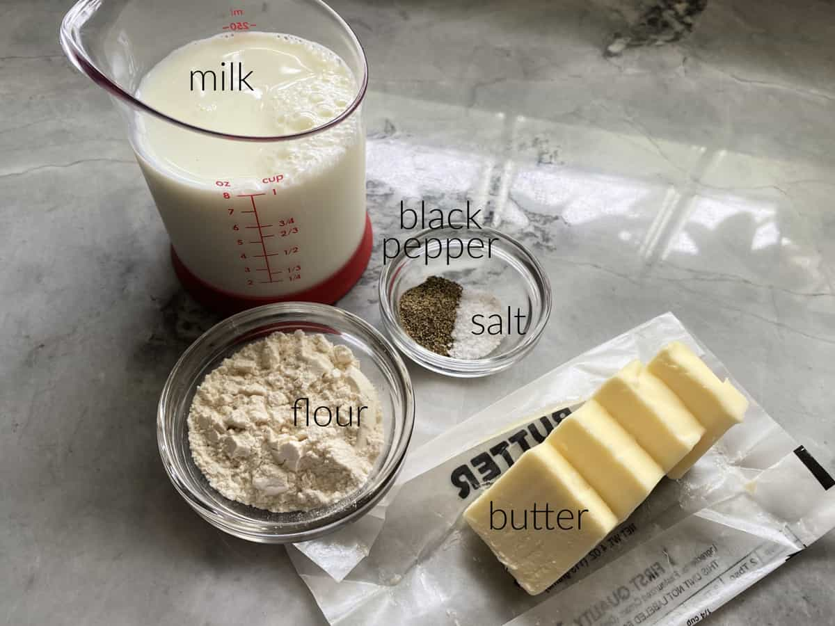 Ingredients on counter: milk, flour, black pepper, salt, and butter.