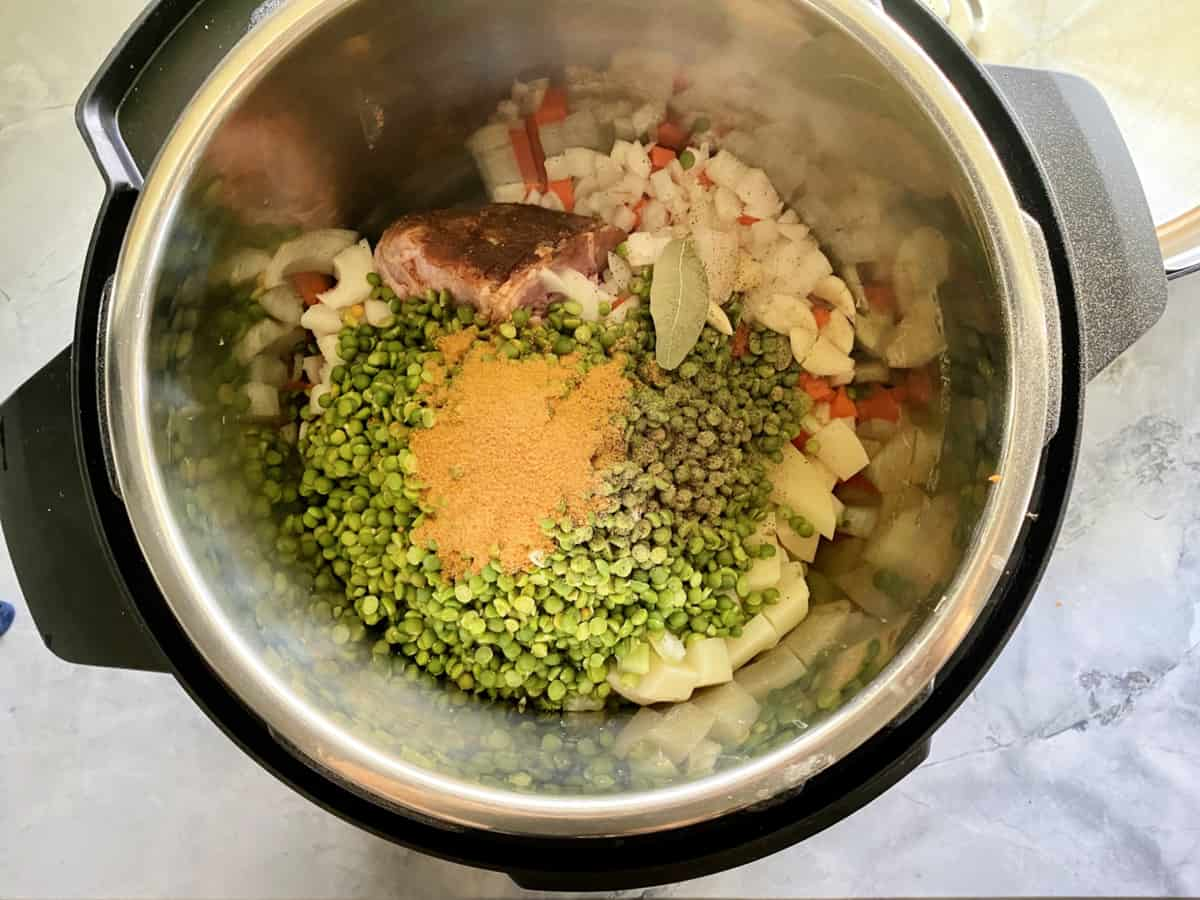 Top view of green split peas, seasoning, ham, onions, carrots, and bay leaf in an Instant Pot.