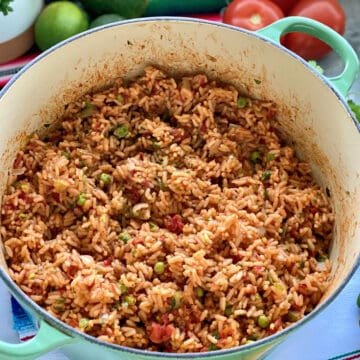 Green pot filled with Mexican Rice with vegetables on the side.