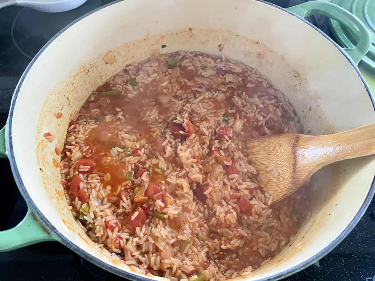Sauce pot with rice and tomatoes with wooden spoon in pot.