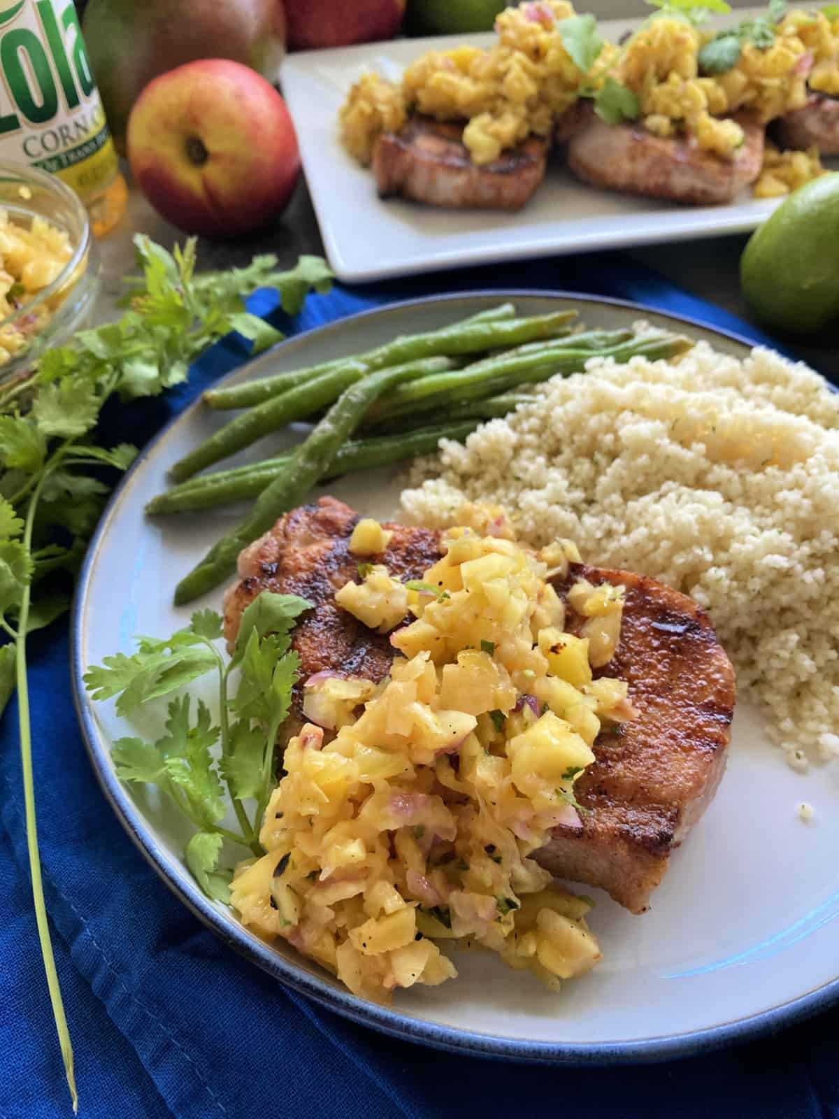 Plate of pork chop with fruit salsa, cilantro, couscous, and green beans.