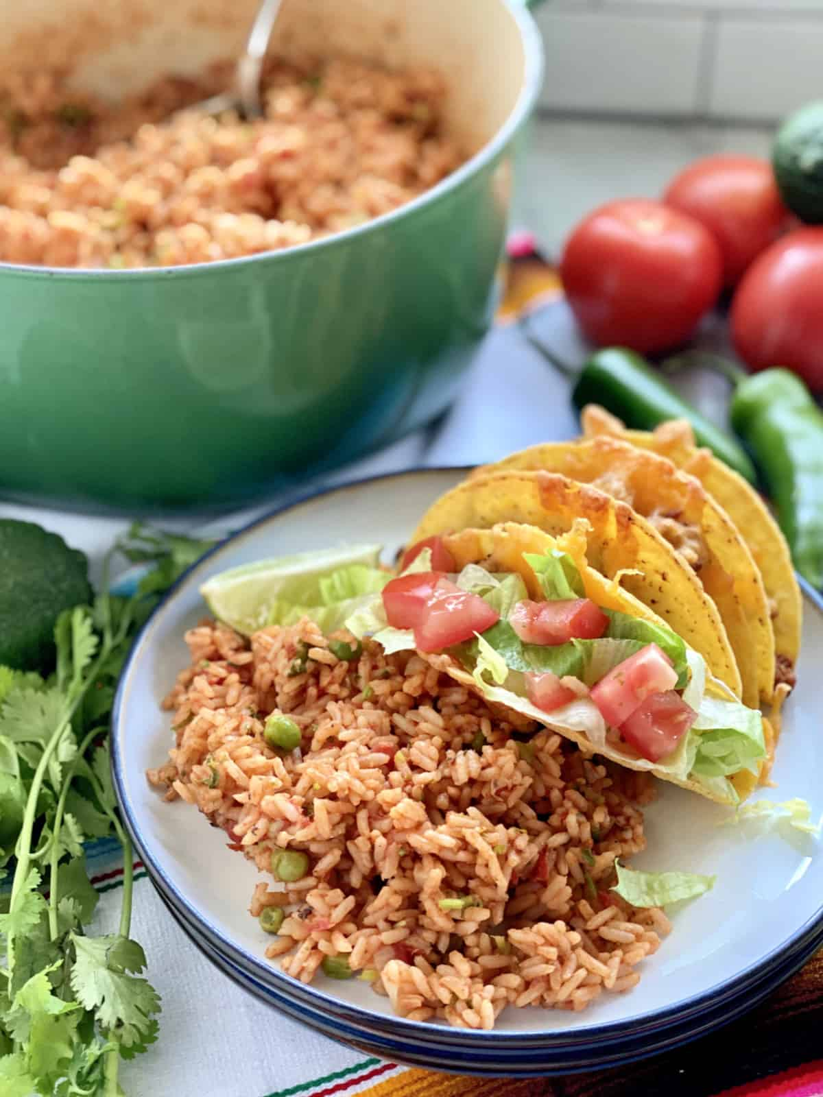 White plate filled with Mexican Rice and tacos with greep pot filled with rice in background.