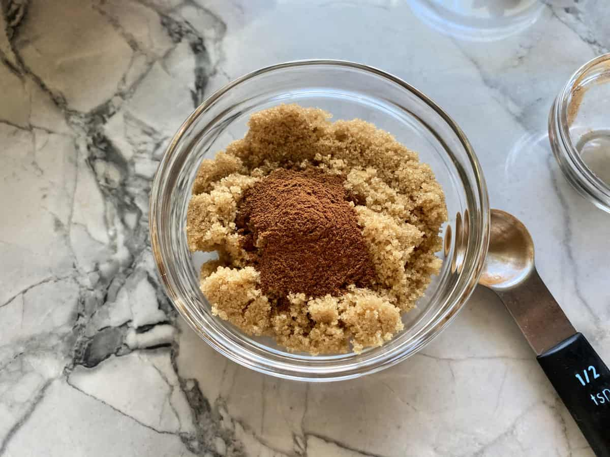 Top view of a glass bowl filled with brown sugar and cinnamon with a ½ teaspoon next to the bowl.