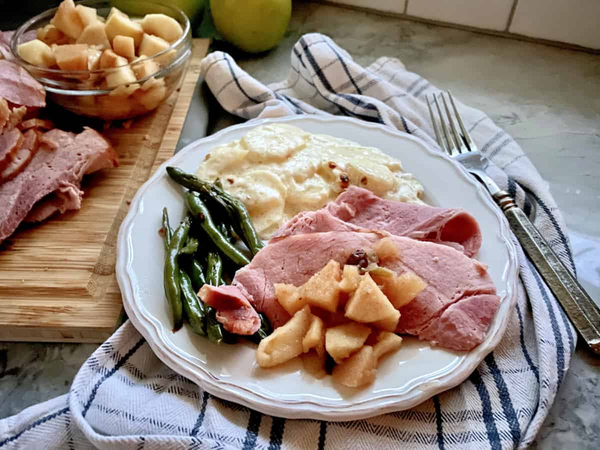 White plate filled with sliced ham, apples, green beans, and potatoes.