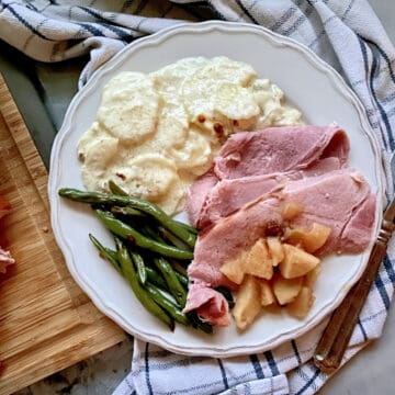 Top view of a white plate on a plaid cloth filled with ham, apples, green beans, and potatoes.