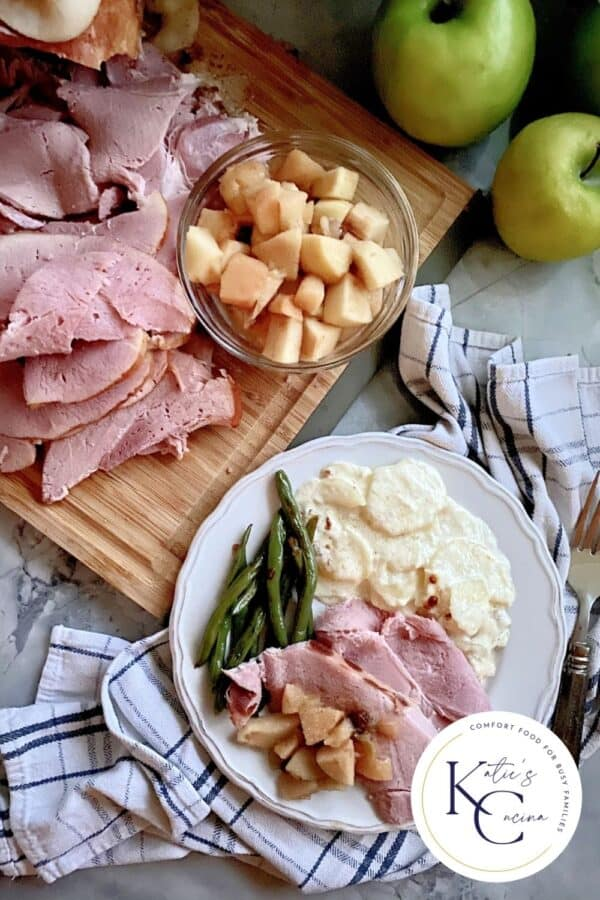 Top view of a ham dinner with potatoes, and green beans and sliced ham and apples on the side.