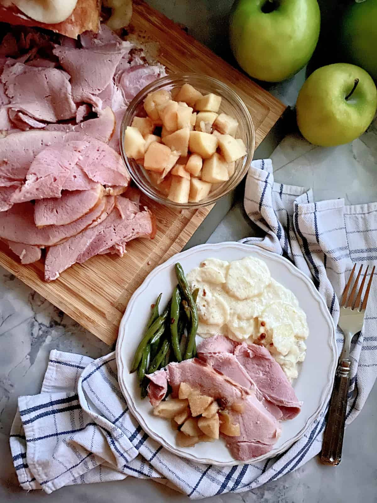 Top view of sliced ham and apple sauce on a cutting board with a dinner plate filled with ham, potatoes, apples, and green beans.