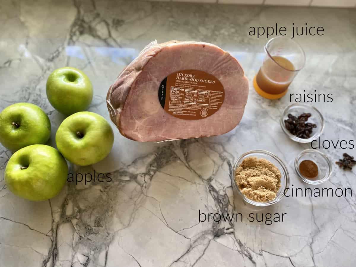 Ingredients on counterl ham, apple juice, apples, brown sugar, cinnamon, cloves, and raisins.