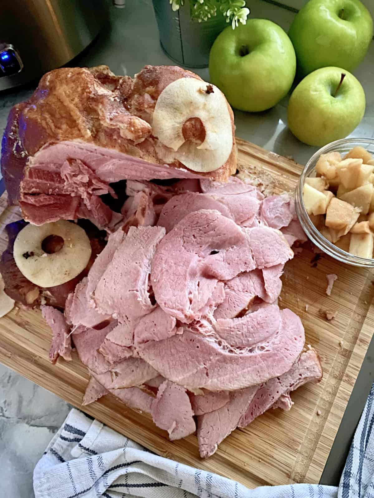 Top view of a wood cutting board with ham slices and a bowl of diced cooked apples next to it.