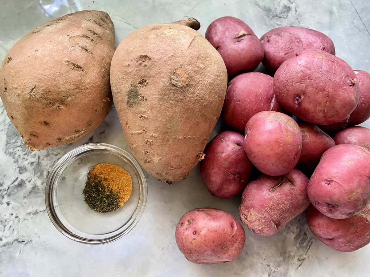 Ingredients on counter: two sweet potatoes, a dozen red potatoes and seasonings.