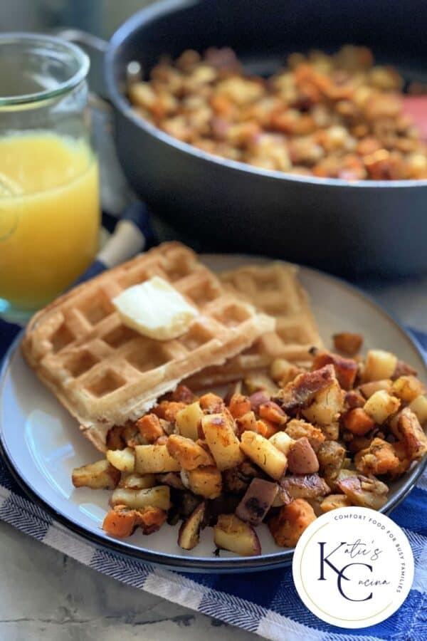 Plate filled with potatoes, waffles with orange juice and a skillet in the background.