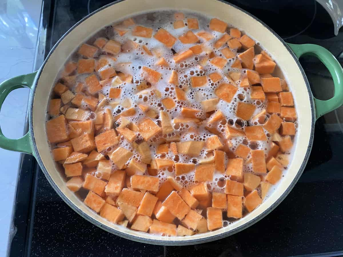 Top view of a green pot filled with diced sweet potatoes in water.