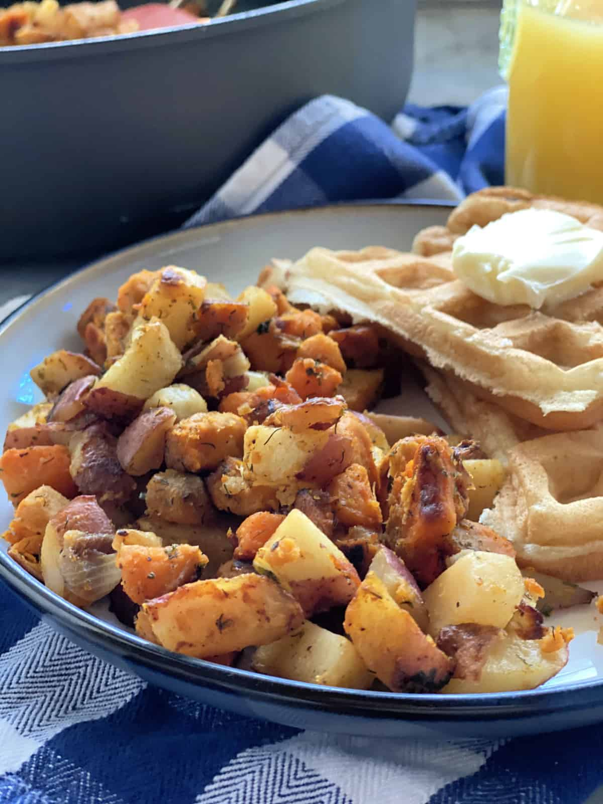 White plate filled with Southern Breakfast Potatoes with buttermilk waffles.