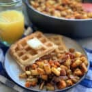 White plate with breakfast potatoes, waffles, and orange juice in the background with a skillet of potatoes.