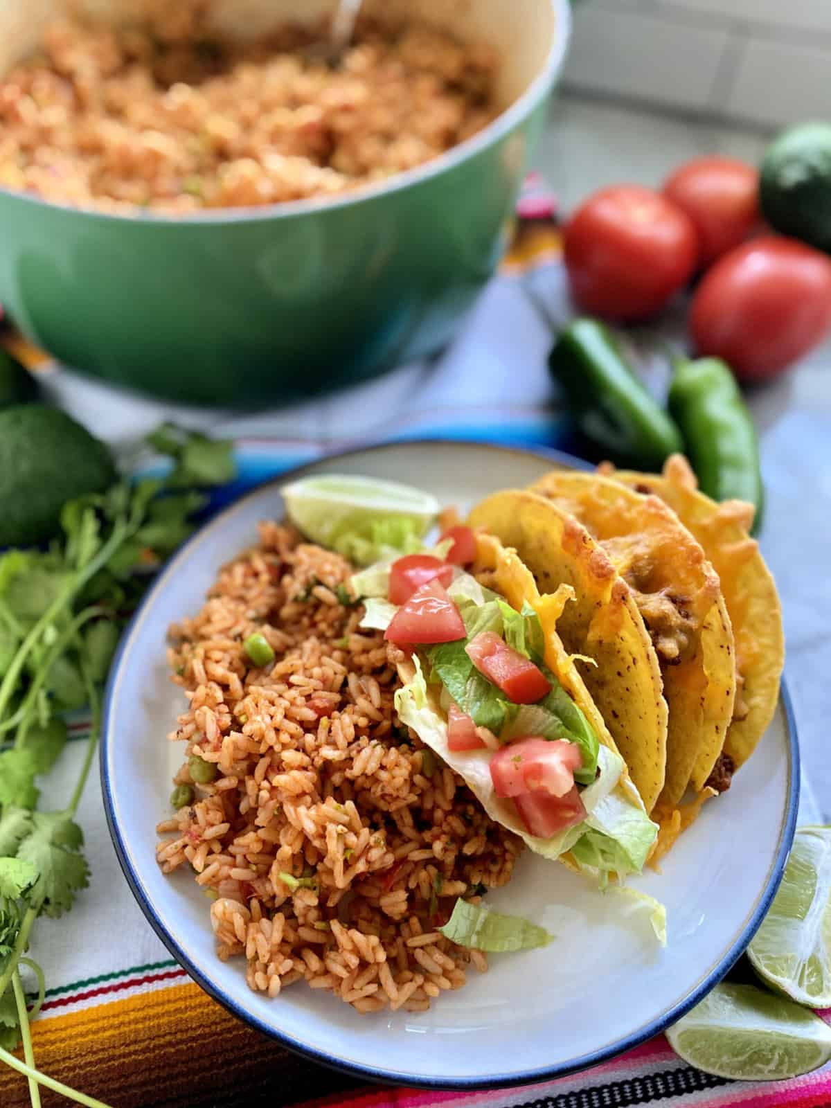 White plate filled with three tacos, Mexican Rice and vegetables in the background.