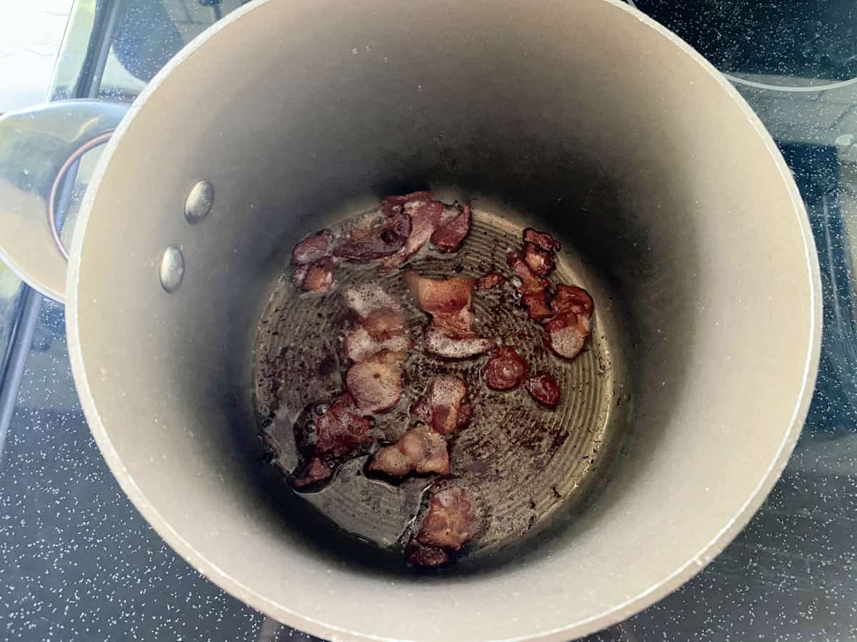 Top view of a brown pot with chopped bacon cooking.