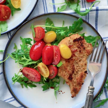 Top view of a plate filled with salad, tomatoes, and breaded chicken with tomatoes on the side.
