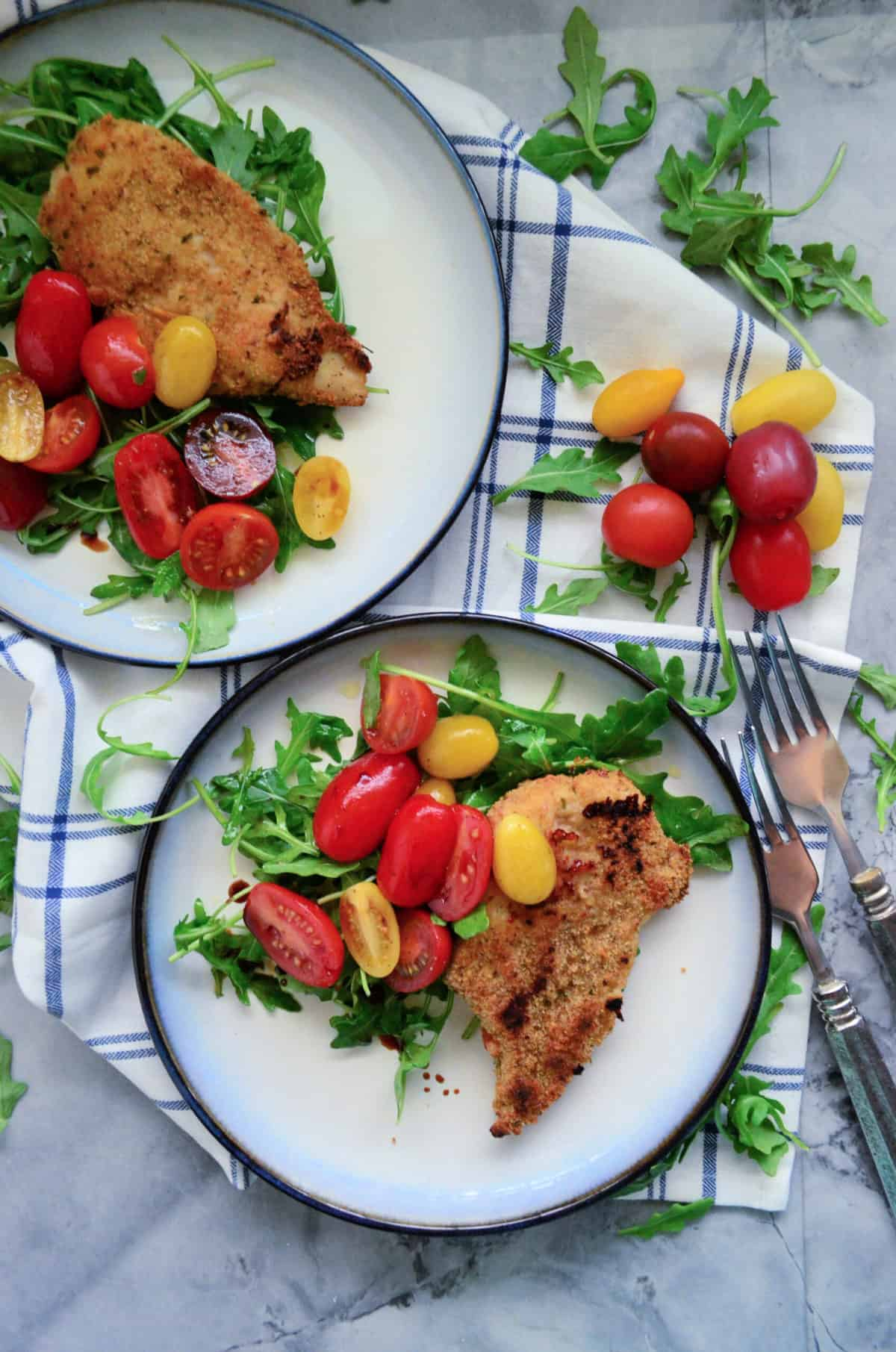 Top view of two white plate with a blue rim filled with arugula and tomato salad with a chicken cutlet on top.