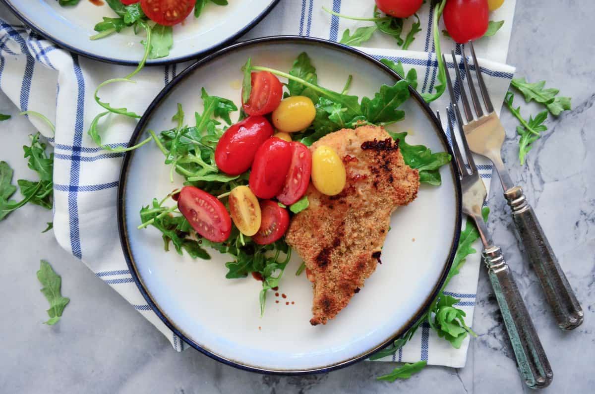 Top view of a white plate filled with an arugula and tomato salad with a chicken cutlet.