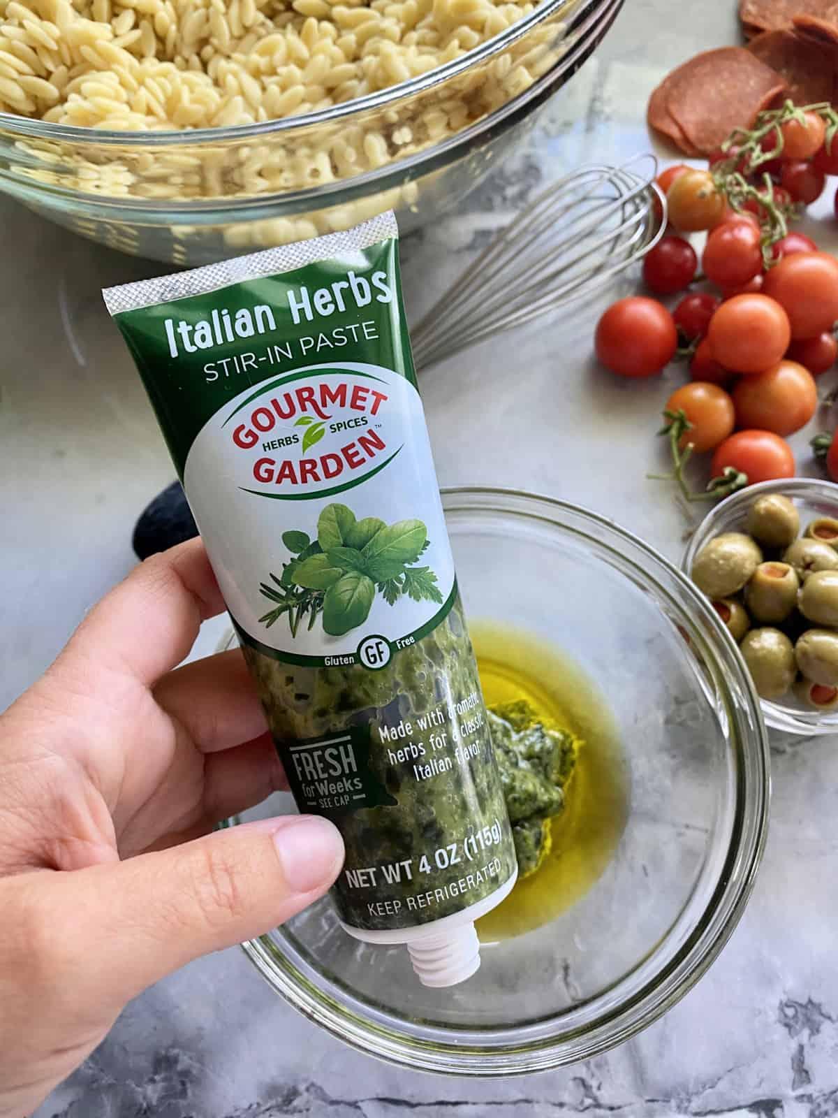 Female hand holding Italian Herb Gorumet Garden Stir-In Paste.