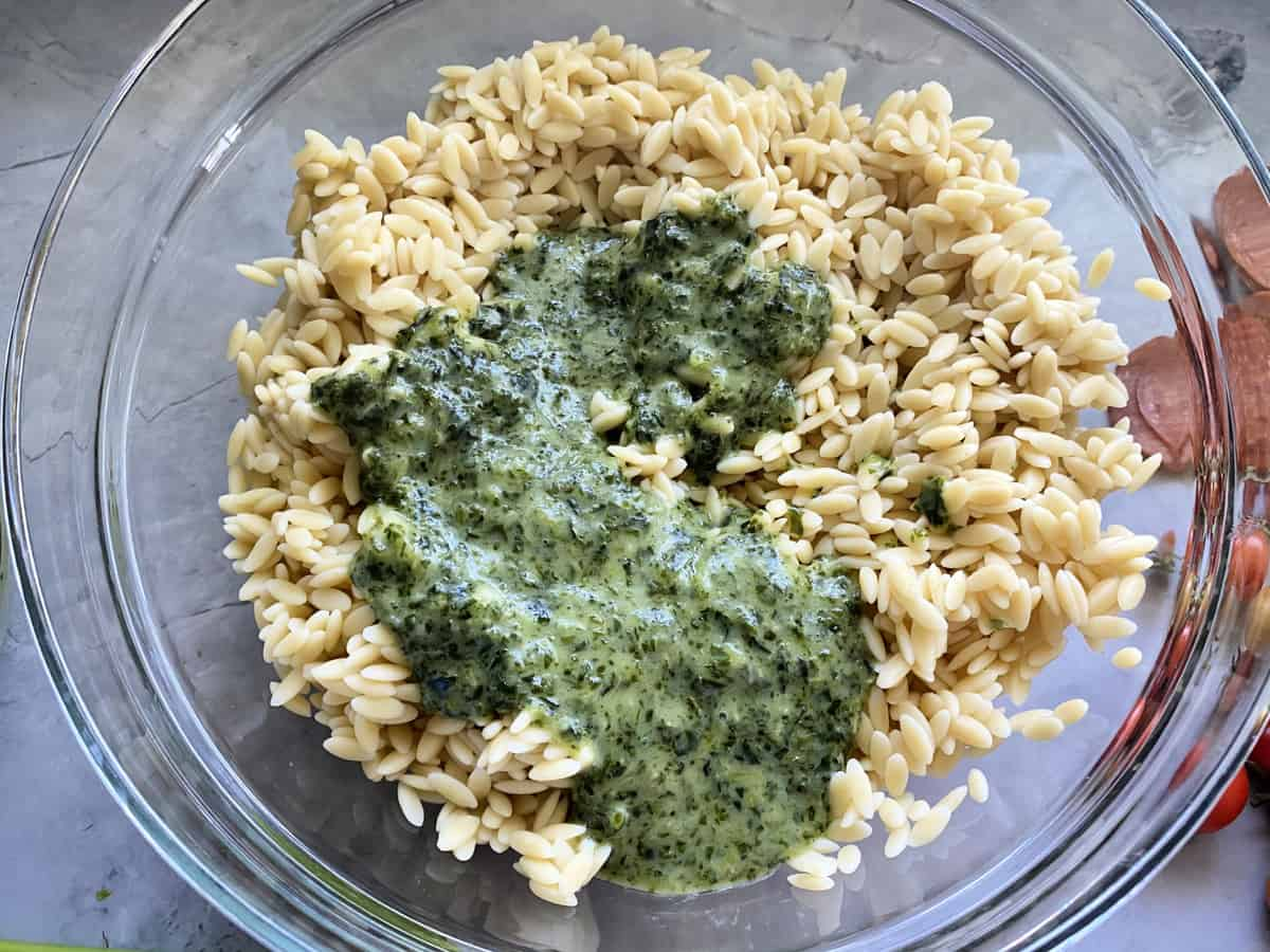 Top view of a glass bowl filled with orzo and Italian herb dressing.