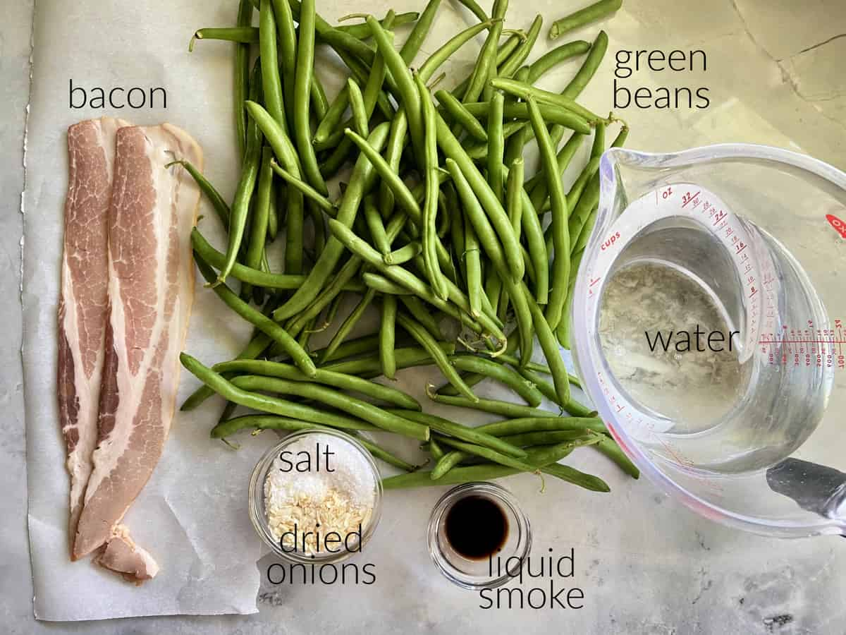 Ingredients on counter, bacon, green beans, salt, onions, liquid smoke, and water.