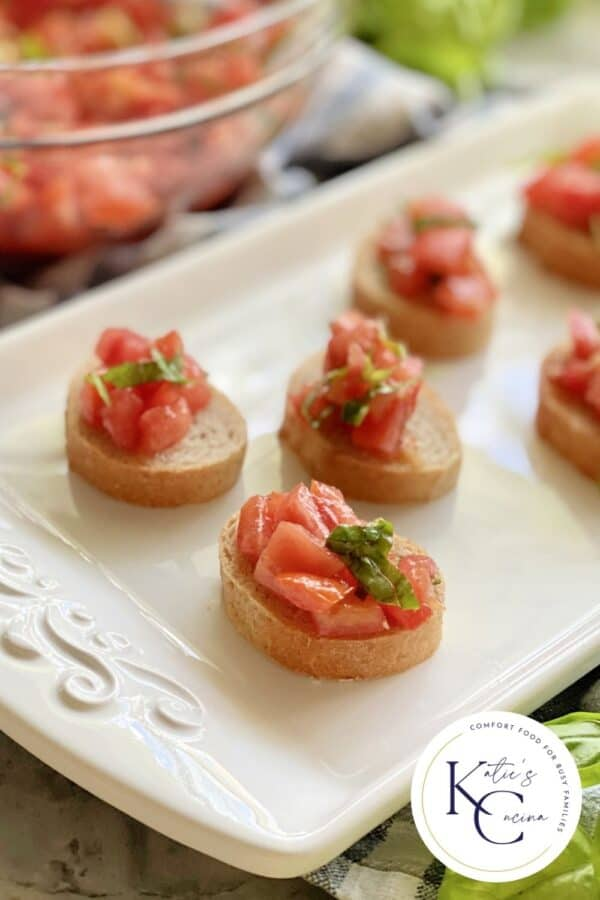 White platter filled with 6 pieces of bruschetta with logo on right corner.