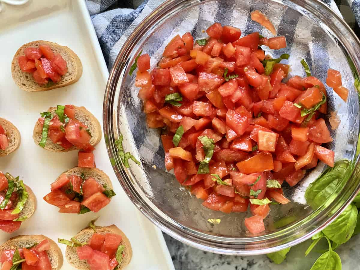 Top view of a glass bowl filled with diced tomatoes, basil, and a platter of bruschetta.
