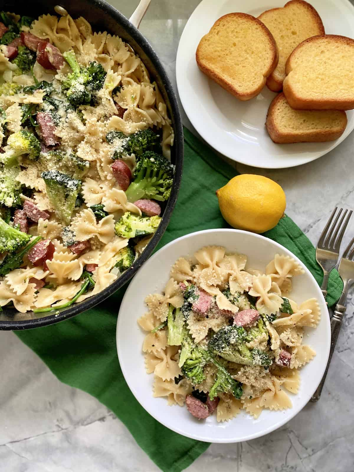 Top view of a black skillet and white bowl filled with bow tie pasta, broccoli, and kielbasa with bread on the side.