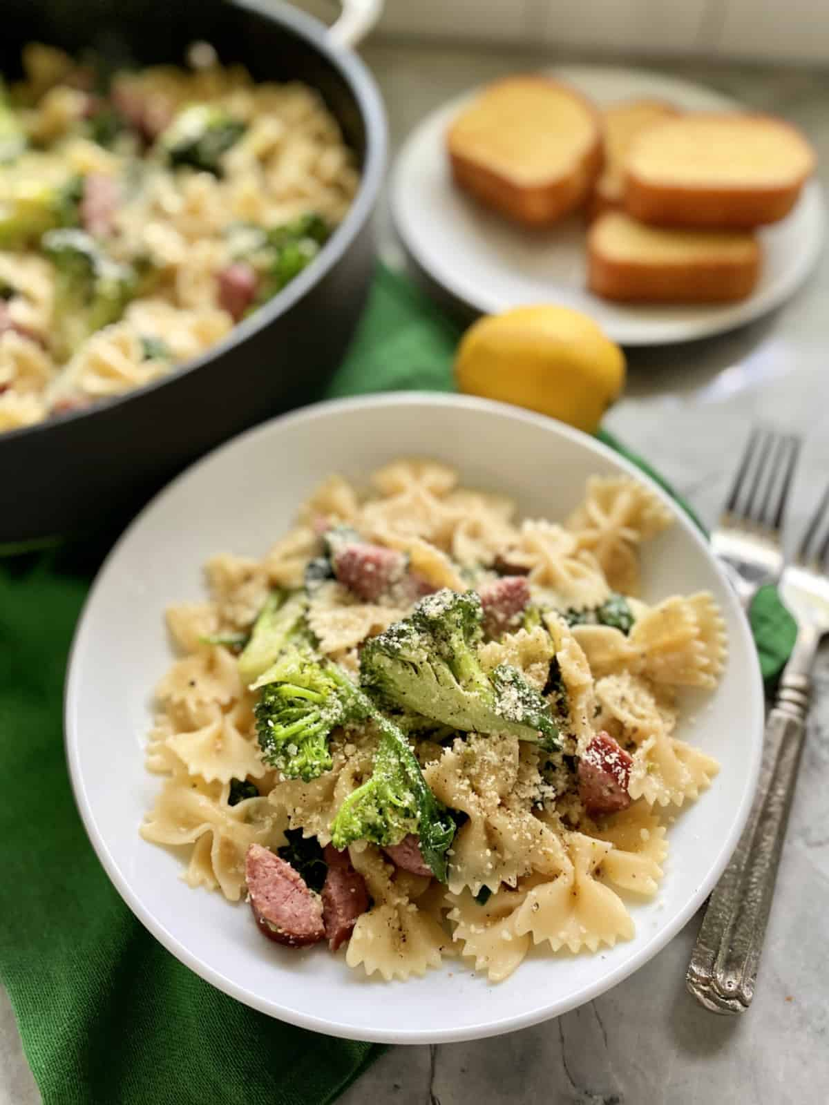 White shallow bowl filled with bow tie pasta, cheese, broccoli, and kielbasa.