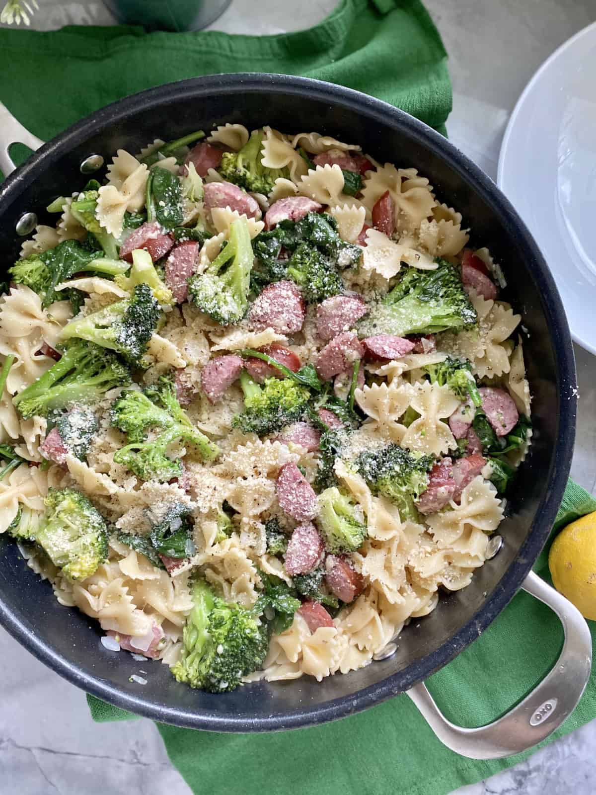 Top view of a black skillet filled with bow tie pasta, broccoli, kielbasa, and cheese.