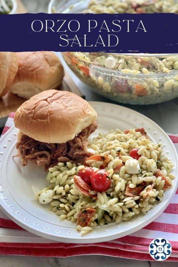 White plate filled with Orzo Pasta Salad and a pulled pork sandwich with recipe title text on image.