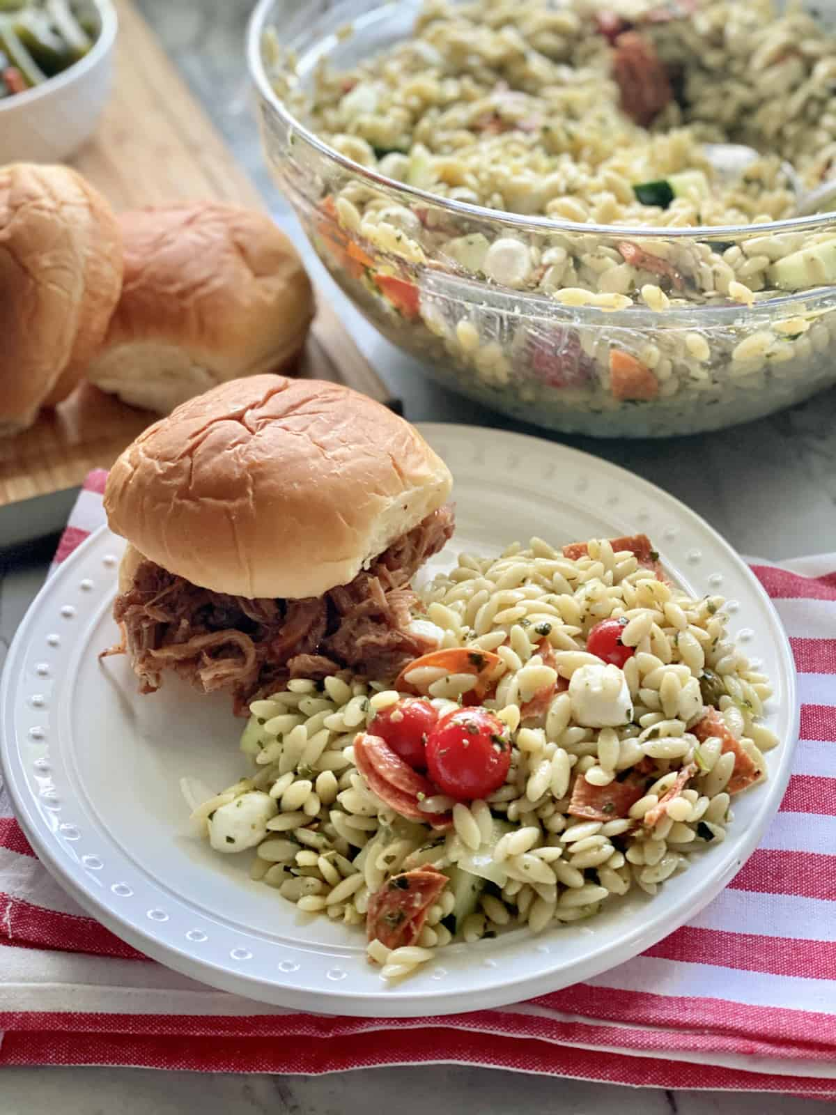 White plate filled with orzo pasta salad with pulled pork sandwich on the plate.