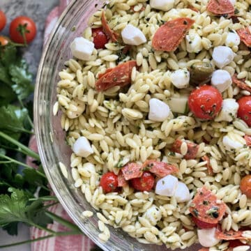 Top view of a glass bowl filled with orzo pasta salad, tomatoes, and mozzarella cheese.