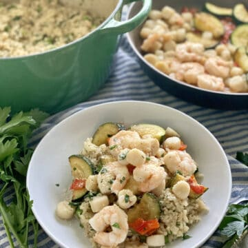 White bowl filled with risotto, shrimp, bay scallops, and zucchini.