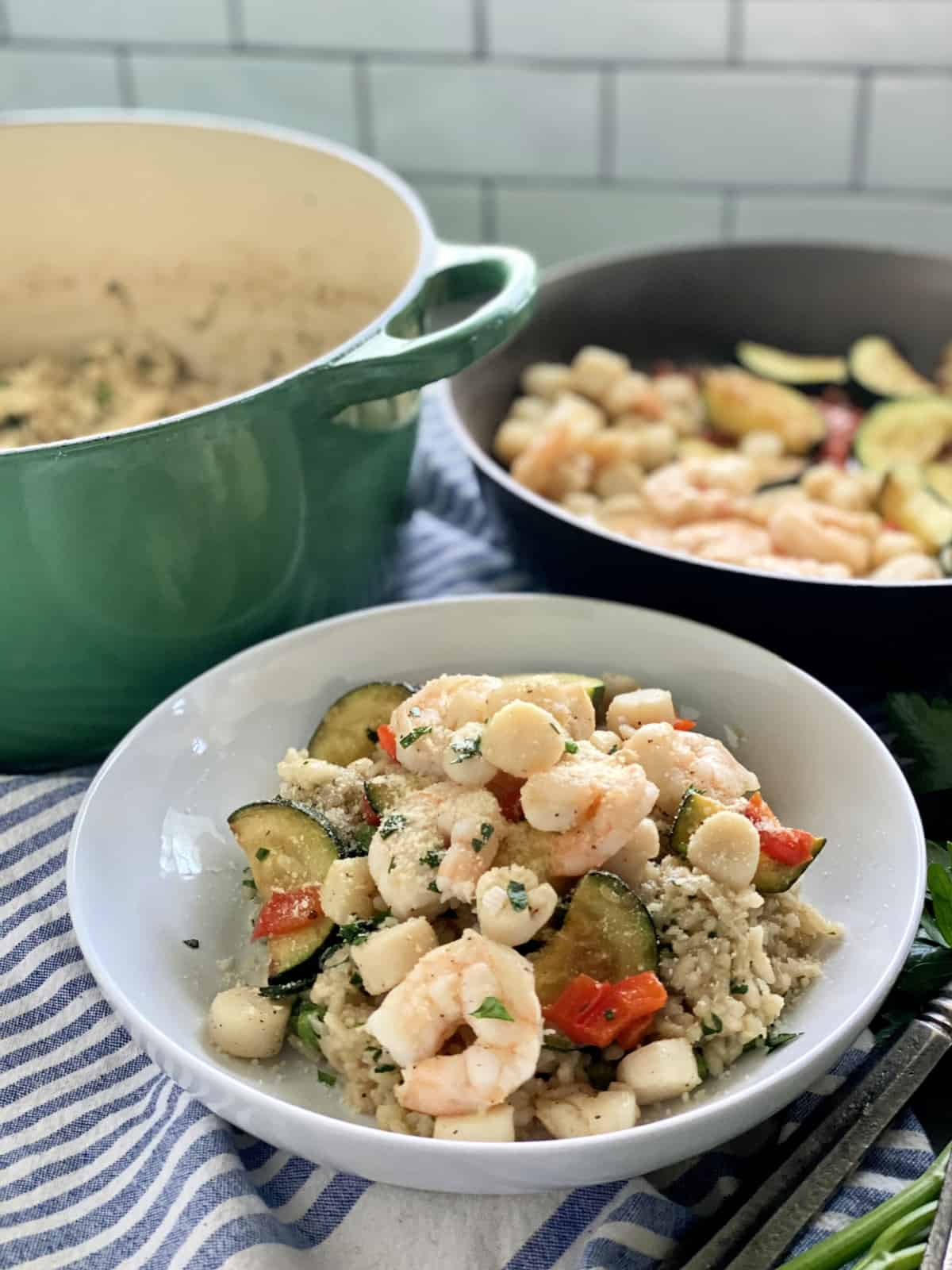 White bowl with seafood risotto with green pot and sauce pan of seafood.