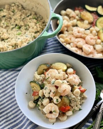 Top view of a white bowl filled with seafood risotto, green pot with risotto, and shrimp in a skillet.