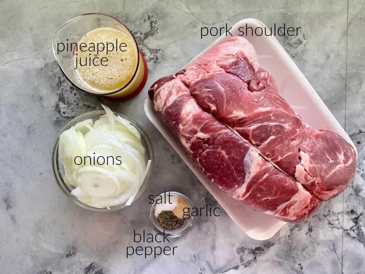 Ingredients on marble countertop: pork shoulder, onions, pineapple juice, salt, pepper, and garlic powder.