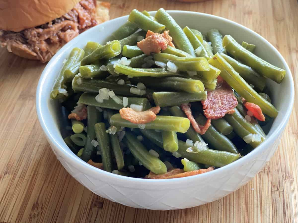 White bowl filled with green beans, onions, and bacon on a wood cutting board.