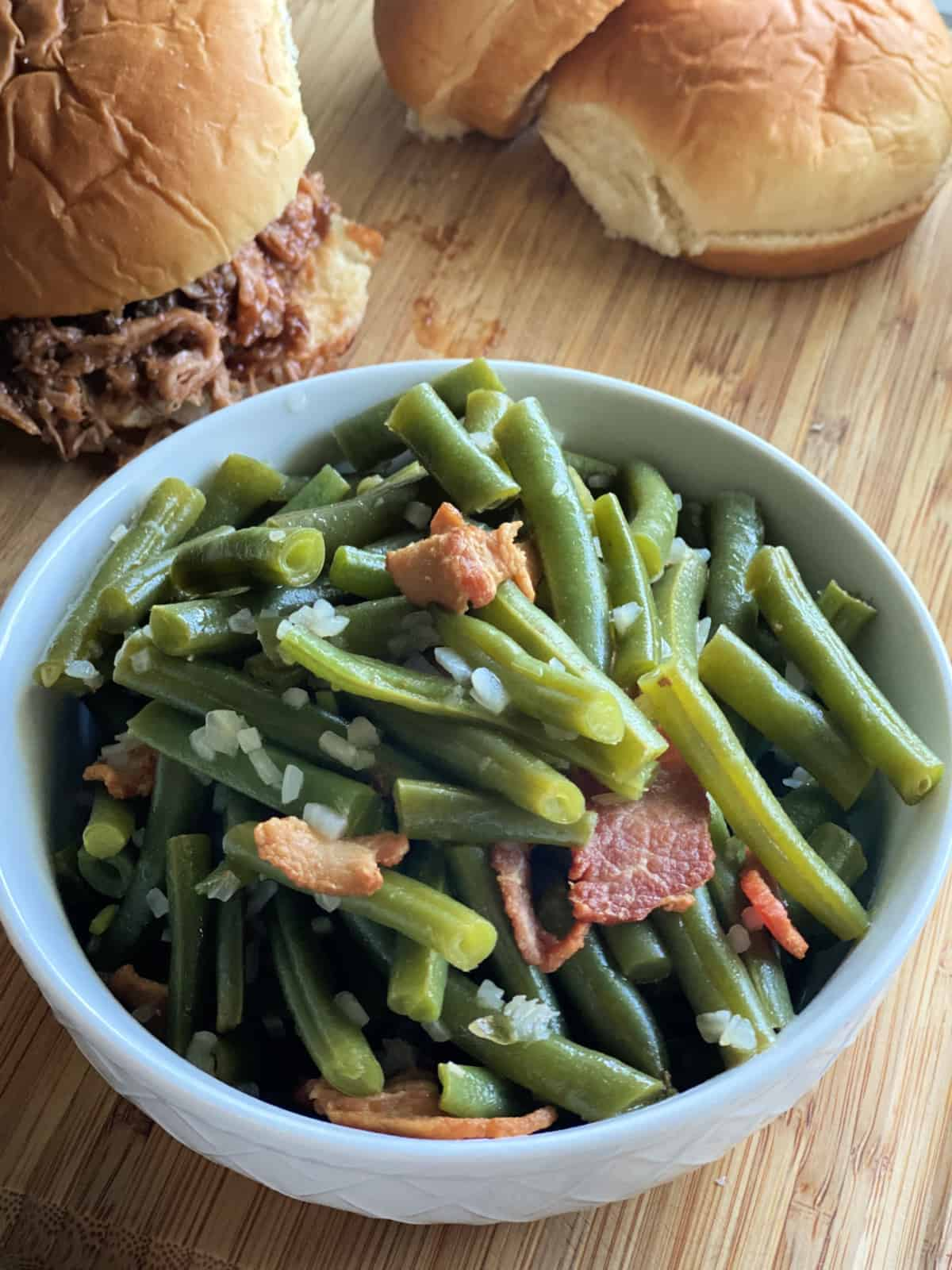 White bowl with chopped green beans, bacon, and onions.