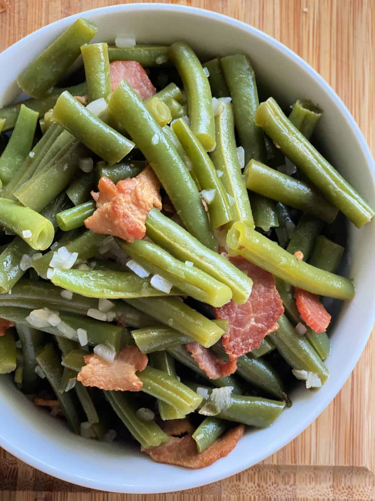 Top view of green beans with bacon and onions on a wood cutting board.