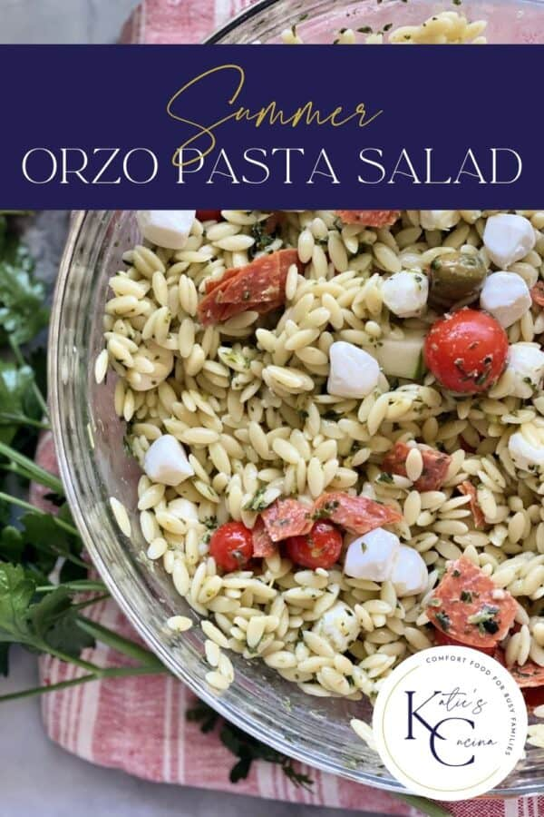 Top view of a glass bowl filled with orzo pasta salad, tomatoes, cucumbers, and mozzarella cheese with text on image for Pinterest.