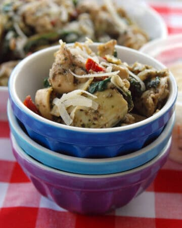 Three bowls stacked with artichoke hearts and tortellinis in it on a red and white checkered table cloth.