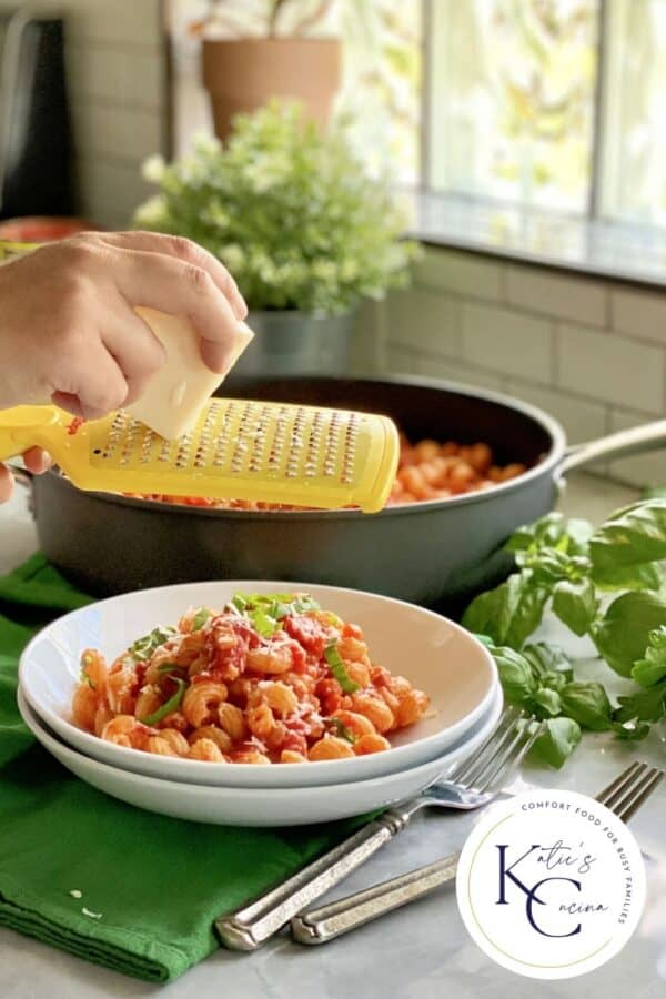 Female hand grating cheese over a bowl of red pasta with logo on right corner.