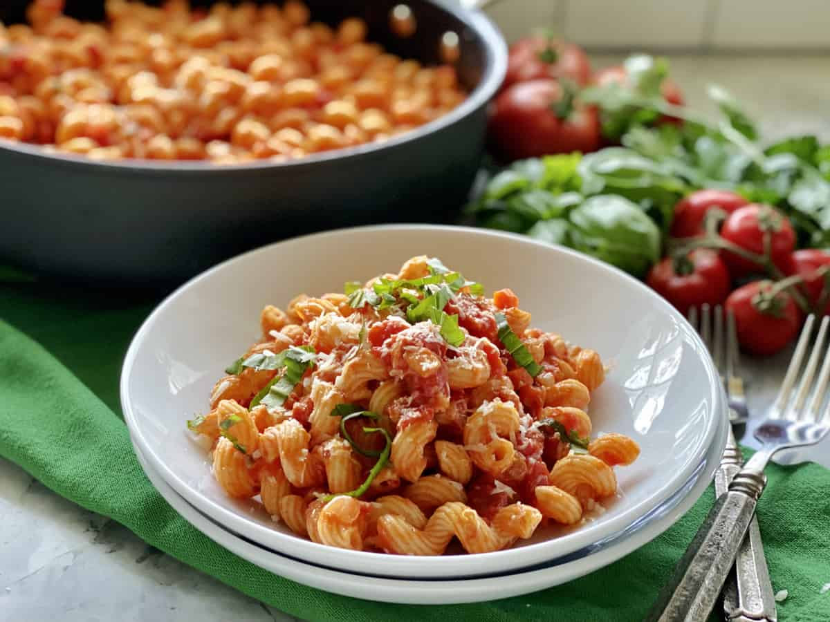 Two white bowls stacked with corkscrew pasta tossed in tomato sauce.