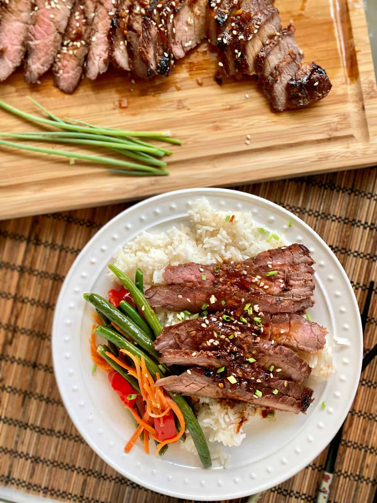 Top view of a white plate filled with slices of steak, rice, and green beans with a wood cutting board with more steak.